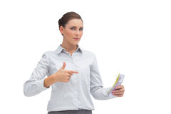 Businesswoman pointing to money in her hand Stock Images