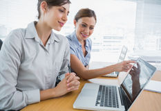Businesswoman pointing to something on laptop for colleague Stock Images