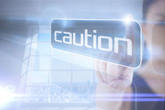 Businesswoman pointing to word caution Stock Image
