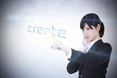 Businesswoman pointing to word create Stock Photos