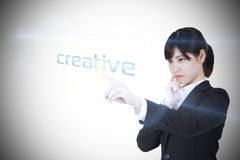 Businesswoman pointing to word creative Stock Photos