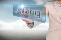 Businesswoman pointing to word stalking. Against cloudy sky background Stock Image