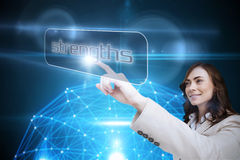 Businesswoman pointing to word strengths. Against glowing sphere on black background Royalty Free Stock Image