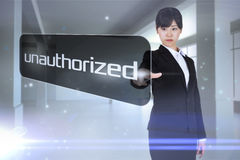 Businesswoman pointing to word unauthorized Stock Photo
