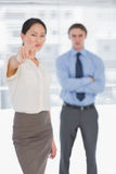 Businesswoman pointing towards camera with man in office Stock Photos