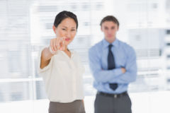 Businesswoman pointing towards camera with man in office Royalty Free Stock Images