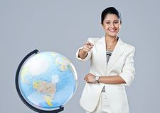 Businesswoman pointing towards globe Stock Image