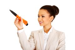 Businesswoman pointing up with big pen. Stock Photo