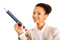 Businesswoman pointing up with big pencil. Stock Images