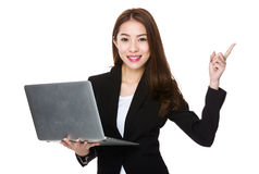 Businesswoman pointing up with pc Stock Images