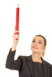 Businesswoman pointing up with pencil. Stock Photo