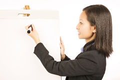 Businesswoman pointing at white blank flipchart Stock Images
