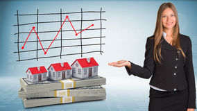 Businesswoman points hand on houses and money Stock Images