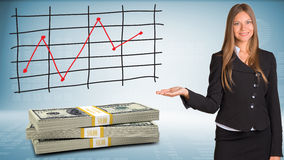 Businesswoman points hand on packs dollars Stock Photo