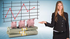Businesswoman points hand on piggy banks and money Stock Photos