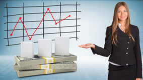 Businesswoman points hand on white boxes and money Stock Photos