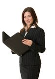 Businesswoman with portfolio. Attractive young brunette woman with long hair wearing black business suit smiles at camera and holds open black portfolio Royalty Free Stock Photo
