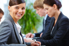 Businesswoman. Portrait of happy employee looking at camera on the background of her colleagues royalty free stock images