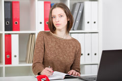 Businesswoman portrait in office using laptop and making notes Stock Images