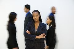 Businesswoman portrait with others. walking by. African-American businesswoman standing with arms crossed while others walk by Stock Image