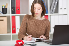 Businesswoman portrait  using laptop and making notes Stock Photo