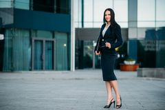 Businesswoman poses against business center. Smiling businesswoman poses against business center. Modern financial building, cityscape. Successful female Royalty Free Stock Image
