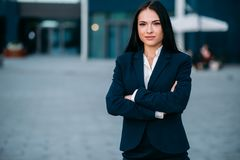 Businesswoman poses against business center. Smiling businesswoman poses against business center. Modern financial building, cityscape. Successful female Royalty Free Stock Images
