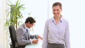 Businesswoman posing from the camera. With a colleague in background working stock footage