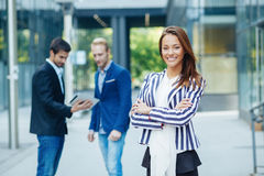 Businesswoman posing in front of a small group of business Royalty Free Stock Images