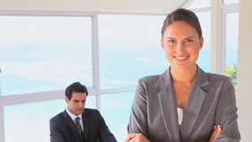 Businesswoman posing while her colleague is at his desk. With the ocean in background stock footage