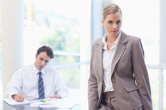 Businesswoman posing while her colleague is working Royalty Free Stock Photography