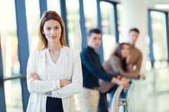 Businesswoman posing while others business people talking Royalty Free Stock Image
