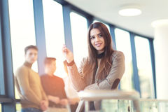 Businesswoman posing while others business people talking Stock Image