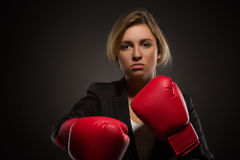 Businesswoman posing in red-coloured boxing gloves Royalty Free Stock Images