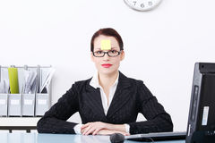 Businesswoman with post it note on her forehead. Stock Image