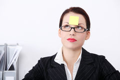 Businesswoman with post it note on her forehead. Stock Photography