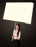 Businesswoman with post-it paper. Young businesswoman holding a big, white post-it paper Royalty Free Stock Images