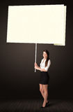 Businesswoman with post-it paper. Young businesswoman holding a big, white post-it paper Stock Image