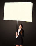 Businesswoman with post-it paper. Young businesswoman holding a big, white post-it paper Royalty Free Stock Photos