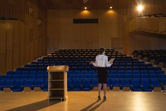 Businesswoman practicing and learning script while standing in the auditorium. Rear view of blonde Caucasian businesswoman practicing and learning script while stock photos