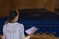 Businesswoman practicing and learning script while standing in the auditorium. Rear view of blonde Caucasian businesswoman practicing and learning script while royalty free stock image