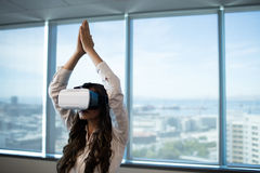 Businesswoman practicing yoga with arms raised while using virtual reality glasses Royalty Free Stock Image