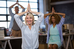 Businesswoman practicing yoga with coworkers Royalty Free Stock Photography