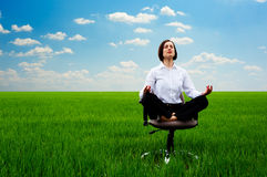 Businesswoman practicing yoga at the meadow Stock Image