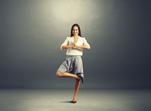 Businesswoman practicing yoga over dark Royalty Free Stock Image