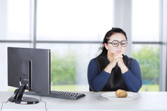 Businesswoman praying with boiled potato Royalty Free Stock Image