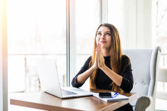 Businesswoman praying. Thoughtful woman in formalwear holding hands clasped and looking up near laptop while sitting at Royalty Free Stock Photo