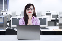 Businesswoman praying while working 3 Stock Photos