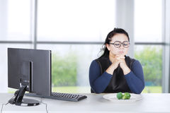 Businesswoman prays with broccoli on plate Royalty Free Stock Photography