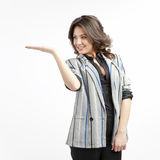 Businesswoman presenting. Young businesswoman dressed in office outfit, presenting something on white background royalty free stock photo